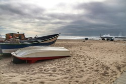 Fishing boats stranded on Aguda beach and Giant waves breaking on the breakwater and the lighthouse on Aguda Beach