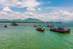 Fishing boats tied by the sandy beach in a fisherman village and a blur background of trees along the beach and mountain from afar at noon