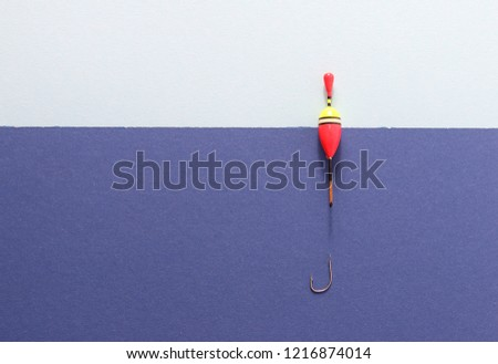 Fishing bobber on blue background. Picture with space for your text.