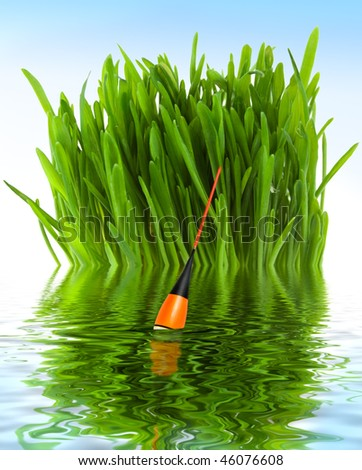 Fishing float in the water against the background of green grass - stock photo