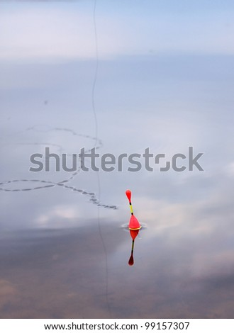 Fishing float on a water unruffled surface