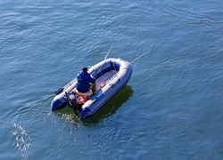 Fishing from an inflatable rubber boat on the river, top view