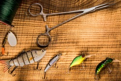 Fishing gear, artificial bait on a predator on a wooden background, top view wobblers and various bait cords and tongs on a wooden background fishing concept with copyspace