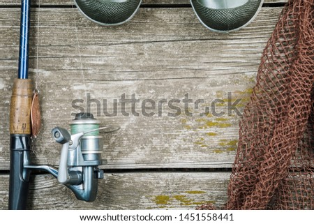 Fishing gear, hooks and baits on a wooden background. #1451558441