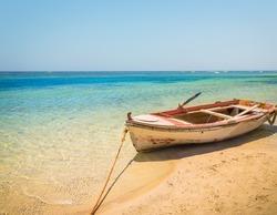 Fishing greek boat docked to coast on the beautiful beach of Crete, Greece
