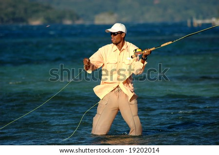 Fishing guide in Honduras shows concentration while casting a heavy fly, which can be seen moving from left to right, in front of his head. He is knee deep in sea water standing on the flats
