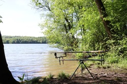 Fishing hobby. Fishing rods on a stand by the lake. Fishing stand with fishing rods by the water.