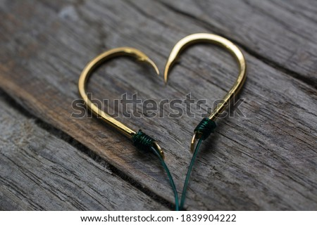 Fishing hooks set in the shape of a heart on a wooden background. ストックフォト ©