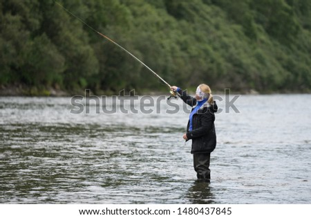 Fishing in Bystraya River in Kamchatka. Woman in special rubber equipment angling in the middle of the stream. He throws trolling spoon and hopes to catch some fish. Greenery around him. Russia.