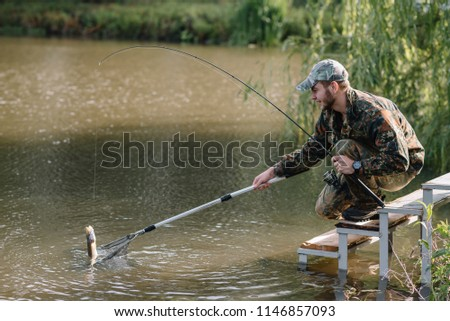 Fishing in river.A fisherman with a fishing rod on the river bank. Man fisherman catches a fish pike.Fishing, spinning reel, fish, Breg rivers. - The concept of a rural getaway. Article about fishing. #1146857093
