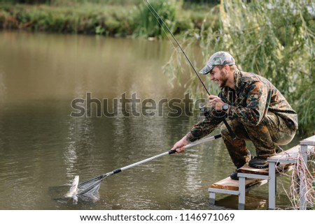 Fishing in river.A fisherman with a fishing rod on the river bank. Man fisherman catches a fish pike.Fishing, spinning reel, fish, Breg rivers. - The concept of a rural getaway. Article about fishing. #1146971069