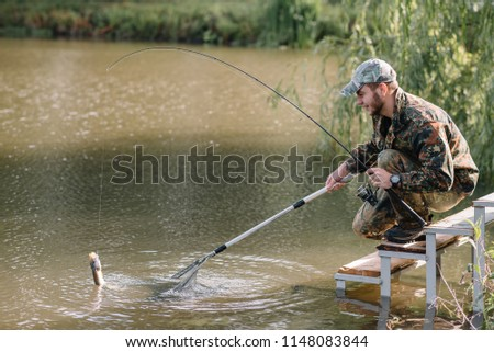 Fishing in river.A fisherman with a fishing rod on the river bank. Man fisherman catches a fish pike.Fishing, spinning reel, fish, Breg rivers. - The concept of a rural getaway. Article about fishing. #1148083844