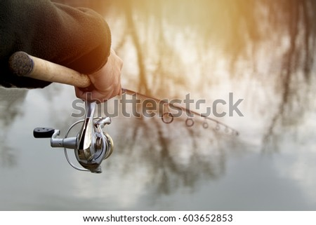 Fishing in river.A fisherman with a fishing rod on the river bank. Man fisherman catches a fish #603652853