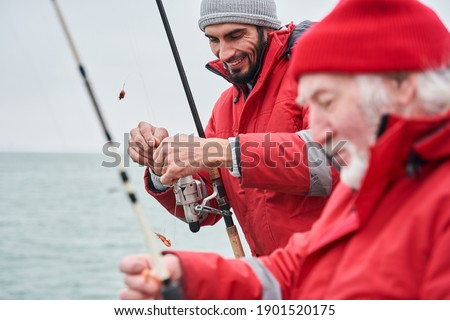 Fishing in the ocean. Side view of the two male colleagues standing on a boat with fishing rod and hook the bait while fishing at the deep sea. Saltwater fishing concept