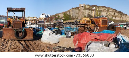 Fishing industry on beach. bulldozer and pollution. Hastings town, cliffs and funicular lift