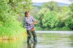 Fishing is fun. mature man fly fishing. man catching fish. summer weekend. Big game fishing. retired bearded fisher. Trout bait. fisherman with fishing rod. hobby and sport activity. pothunter.