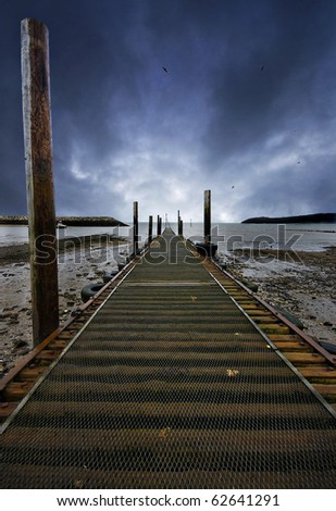 fishing jetty at low tide with vanishing point at the bright part of a threatening sky