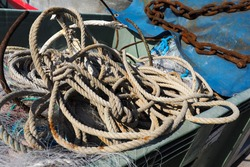 Fishing kit. Rusty anchor chain, rope, and fishing nets lie in the boat on a Sunny day.