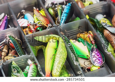 fishing lures and accessories in the box background. Focus in the center of the bait