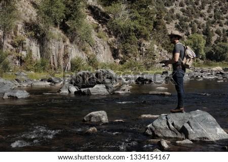 Fishing mountain stream. Fisherman fishing a mountain stream. Angler Standing on rock in mountain river. Fishing western rivers. Fisherman standing on rock  #1334154167