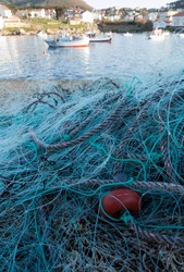 fishing net and floating buoys in a small port with sea and fishing boats in the background on the Costa da Morte Galicia Spain the best fish and seafood in the world