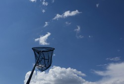 Fishing net, landing net catches a cloud in the blue summer sky.
