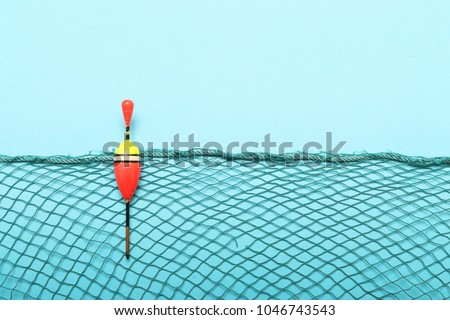 Fishing net with homemade bobber on blue background. Picture with space for your text.