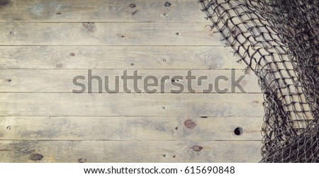 Fishing nets over wooden background with copy space.