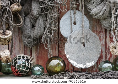 Fishing nets, round stone sinkers, cork and glass floats at boathouse wall in Norway