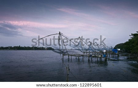 Fishing nets sit in the water near the shore - stock photo