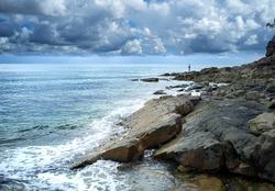Fishing on beautiful landscape beach with rocky shore and dramatic clouds, Noosa Heads, Sunshine Coast, Australia