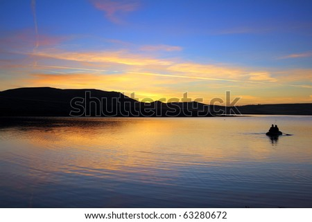 fishing on morning lake with mountain sunrise