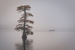Fishing on Reelfoot lake in Tennessee during early morning fog in fall