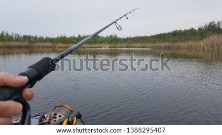 Fishing on the lake on a cloudy day, start of fishing season. rod wheel closeup #1388295407