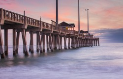 Fishing pier and boardwalk in the Atlantic Ocean at sunrise in Nags Head on the Outer Banks of North Carolina.