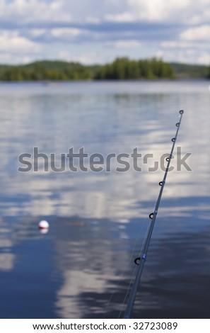 Fishing Pole - bobber floating in lake - stock photo