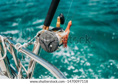 Fishing pole on a sailboat, catching fish while sailing in the Caribbean Sea, blue turquoise water, ocean fish, spinning reel, recreational hobby  #1470097118