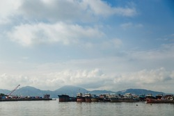 Fishing port in the bay in the early morning with picturesque mountains in the distance against a blue sky with clouds, Shenzhen, China