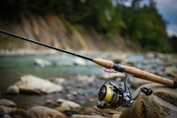 Fishing reel and spinning on stone, blurred background.