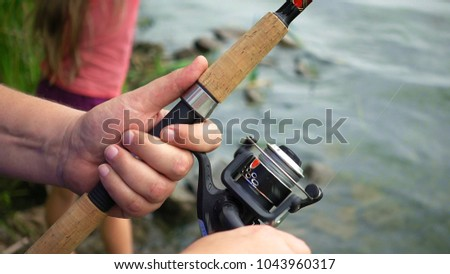 Fishing reel closeup. Man is fishing with spinning fishing rod close to coast shore line. Outdoor recreational activity. #1043960317