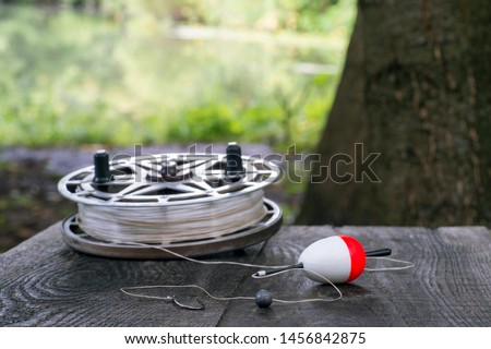 Fishing reel with fishing line, red and white float, hook and sinker on wooden table on natural background. The concept of classic fishing tackle. Text space. #1456842875