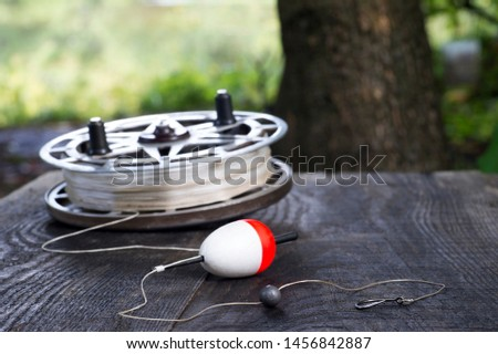 Fishing reel with fishing line, red and white float, hook and sinker on wooden table on natural background. The concept of classic fishing tackle. Text space. #1456842887