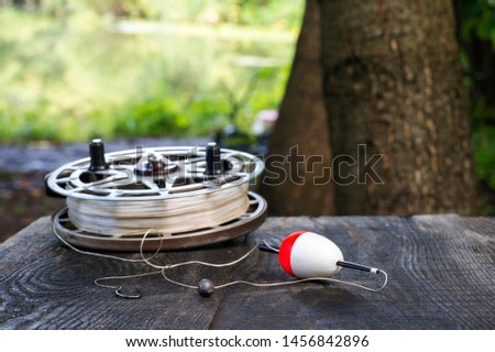 Fishing reel with fishing line, red and white float, hook and sinker on wooden table on natural background. The concept of classic fishing tackle. Text space. #1456842896