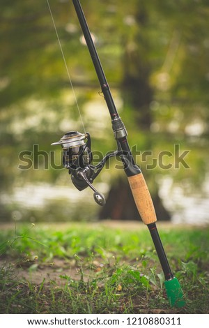 Fishing reel with lake background #1210880311