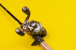 Fishing rod and reel on a yellow background. Casting rod with a multiplier reel. Fishing tackle. Selective focus.