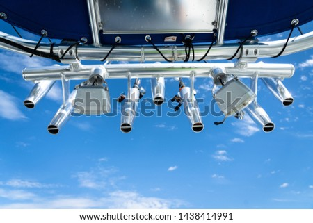 Fishing rod and reels in rod holders underneath a blue sky #1438414991