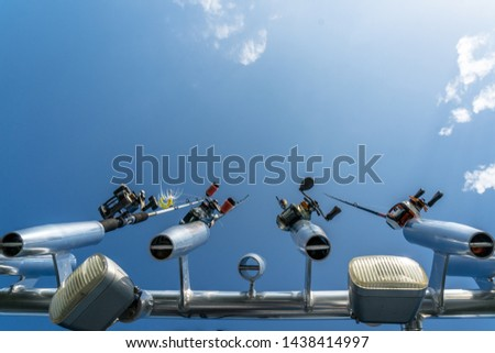 Fishing rod and reels in rod holders underneath a blue sky #1438414997