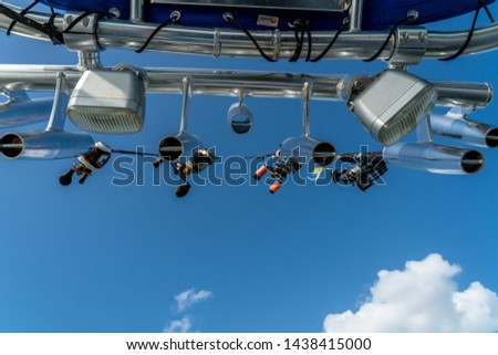 Fishing rod and reels in rod holders underneath a blue sky #1438415000