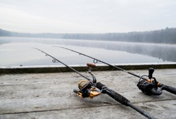 Fishing rod and wheels on the wooden pier, misty fog against the backdrop of lake. The concept of rural getaway. Article about fishing day.
