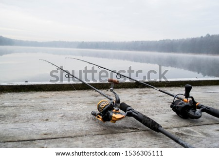 Fishing rod and wheels on the wooden pier, misty fog against the backdrop of lake. The concept of rural getaway. Article about fishing day. ストックフォト ©